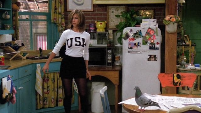 Rachel Green in black shorts with a white shirt that says USA across it.