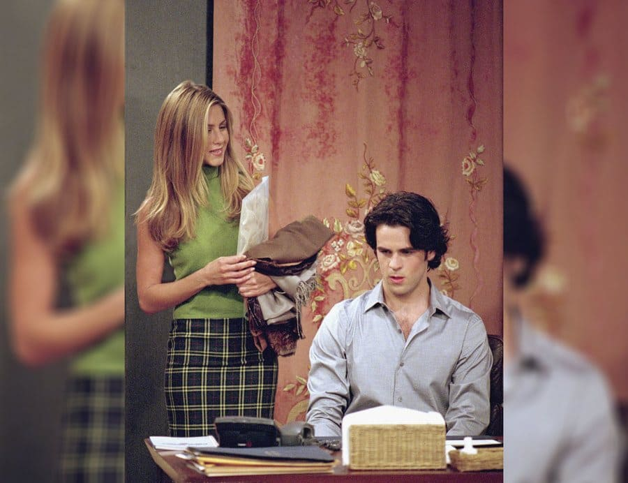 Rachel Green standing with her new assistant played by Eddie Cahill while she wears a green shirt and blue and a yellow plaid skirt.