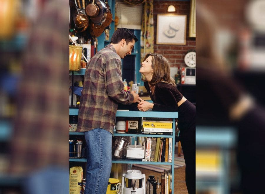 Rachel Green in a black V-neck belly shirt and long black pants leaning over the island towards Ross.