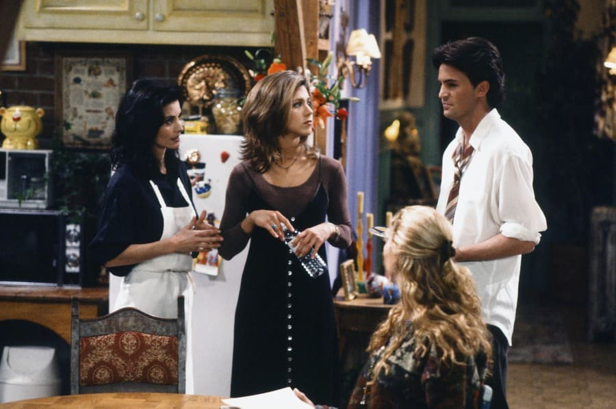 Monica, Chandler, and Phoebe standing around Rachel Green dressed in all black, in a long-sleeved see-through shift with a long V-neck velvet dress with buttons down the front.