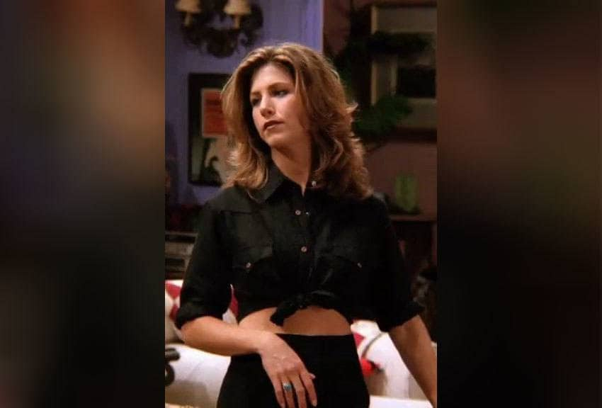 Rachel Green in a button-down black shirt that is tied around her stomach.