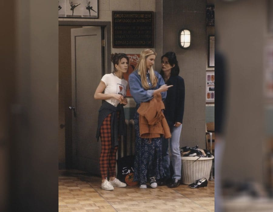 Rachel, Monica, and Phoebe with Rachel in red plaid pants and a white t-shirt.