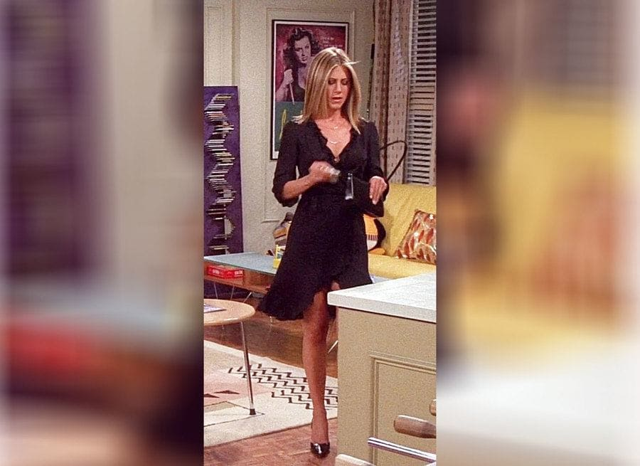 Rachel Green in a short black wrap-around dress with a V-neck.