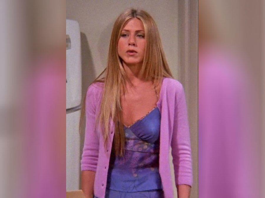 Rachel green in a spaghetti strap purple dress with a light purple sweater.