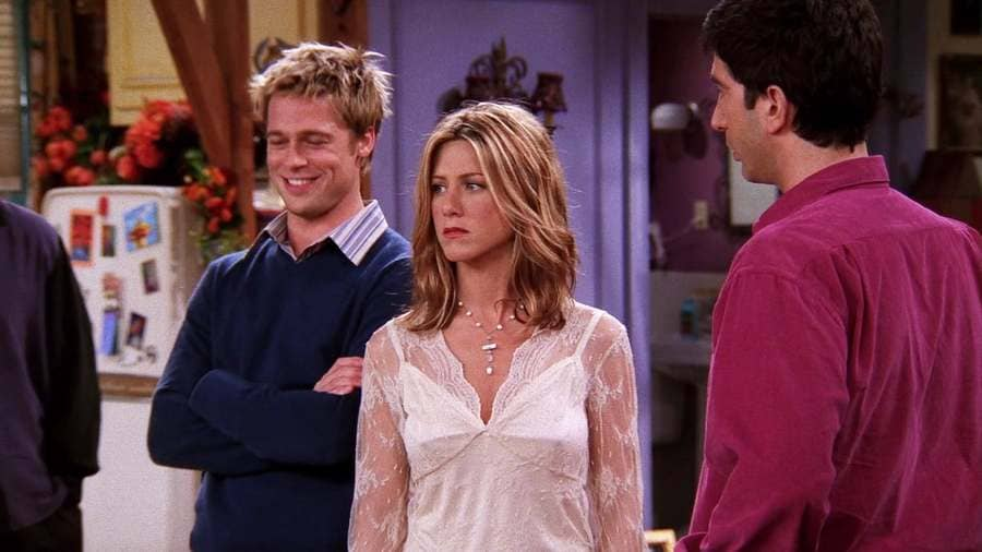 Rachel Green in a lacey blouse with Ross and Brad Pitt standing by her.