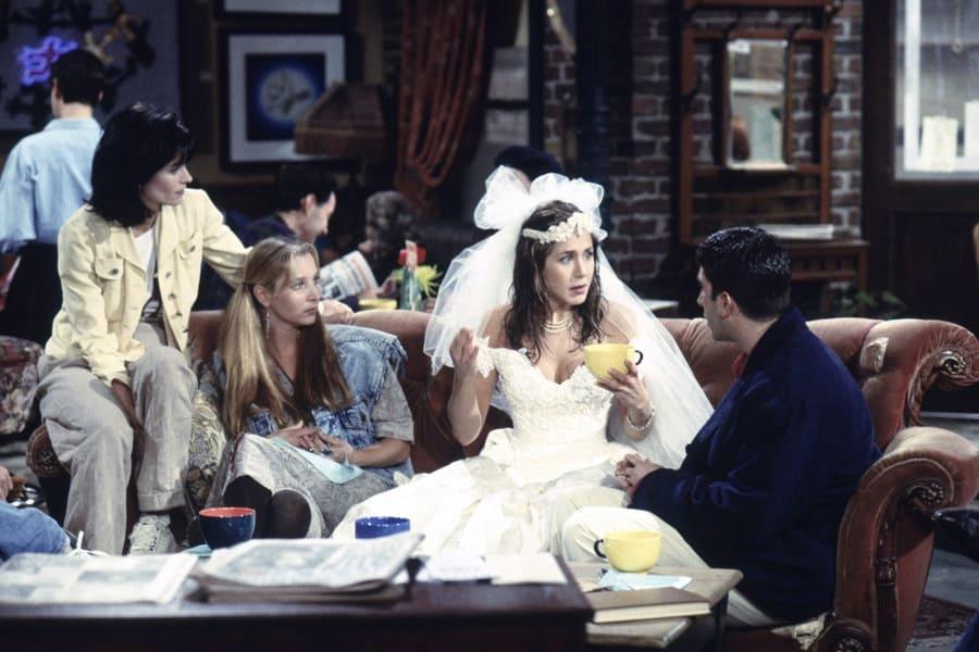 Rachel Green in her wedding dress talking to Monica, Phoebe, and Ross.