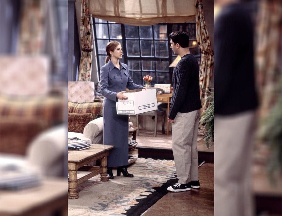 Rachel standing with a long skirt suit on holding a box and speaking with Ross.
