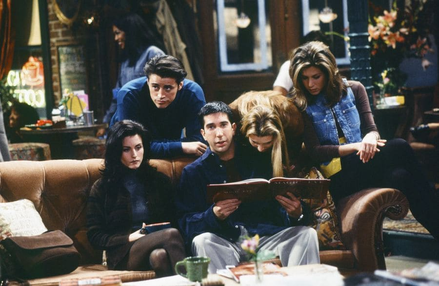 Rachel, Monica, Joey, Ross, and Phoebe sitting in the coffee house with Rachel in a light denim vest.