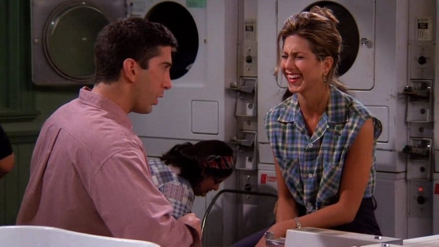 Rachel Green in a blue and green plaid shirt talking to Ross in the laundry room.