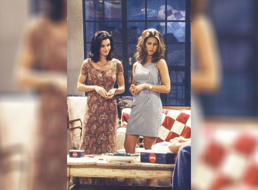 Rachel in a square printed black and white outfit and Monica in a red patterned dress.