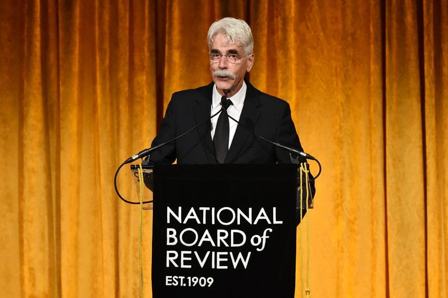 Sam Elliott standing at the podium at the National Board of Review Awards Gala in 2019.