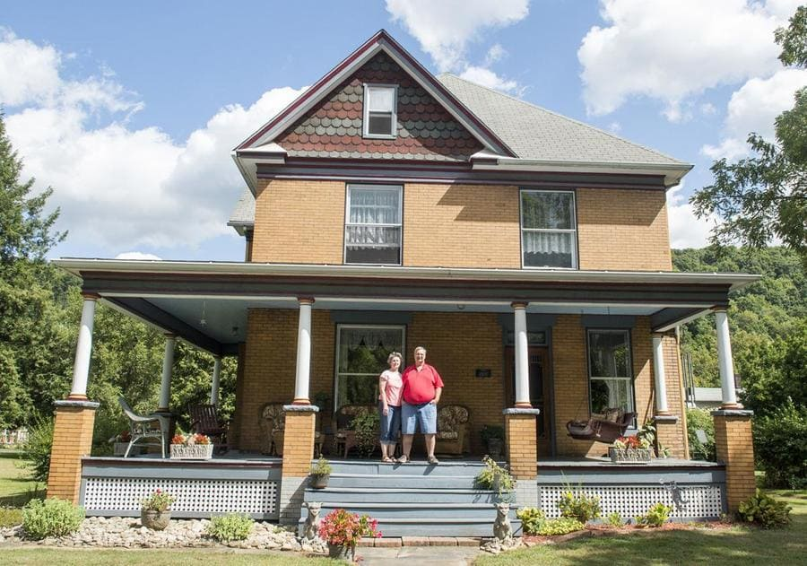Barbara and Scott Lloyd are standing on the porch of their home, which was used in the movie The Silence of the Lambs.