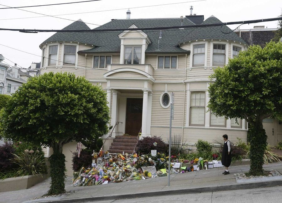 A woman is standing outside of the Mrs. Doubtfire house looking at the memorial for Robin Williams.