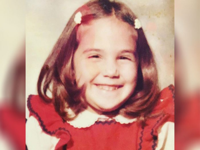 Ricki Lake as a child in a red dress with a white collared shirt.