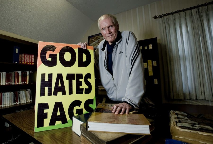 "Fred Phelps, the reverend that Ricki Lake kicked off her show, holding a sign says, ""God Hates Fags."""