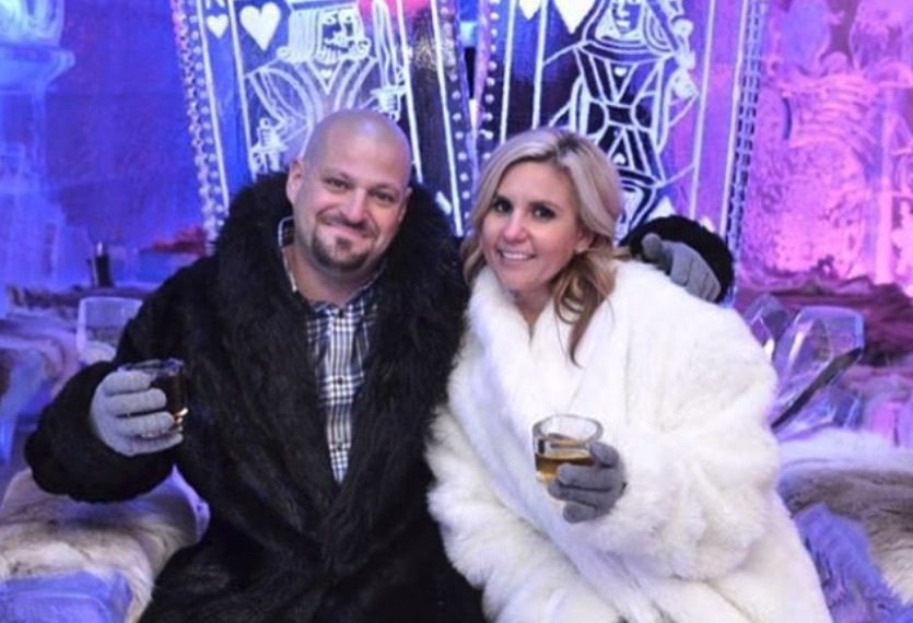 Brandi and Jarrod at an event with an ice sculpture in the background.