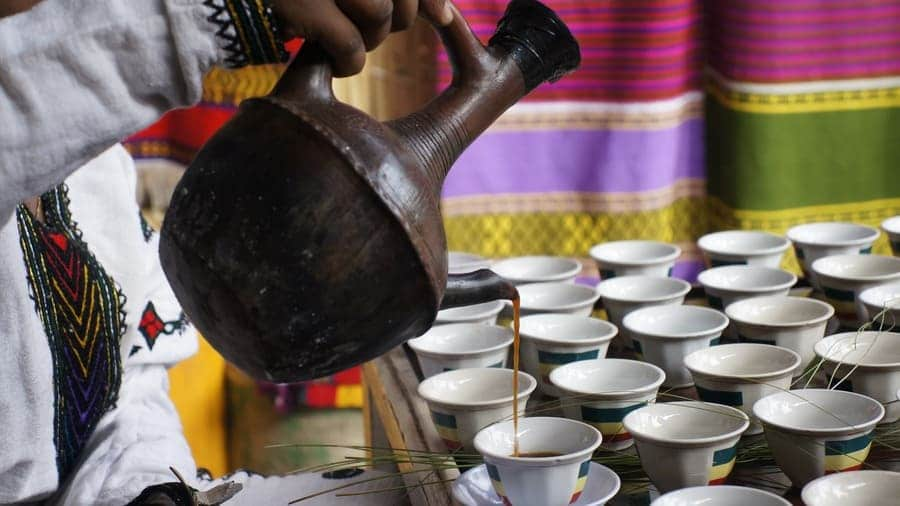 Photograph of the Ethiopian coffee culture, a lot of coffee mugs set out, and a woman is pouring coffee for everyone from an older jug.