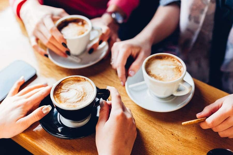 Close up of three friends having coffee