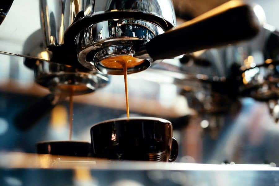 A close-up of espresso pouring out of a coffee machine