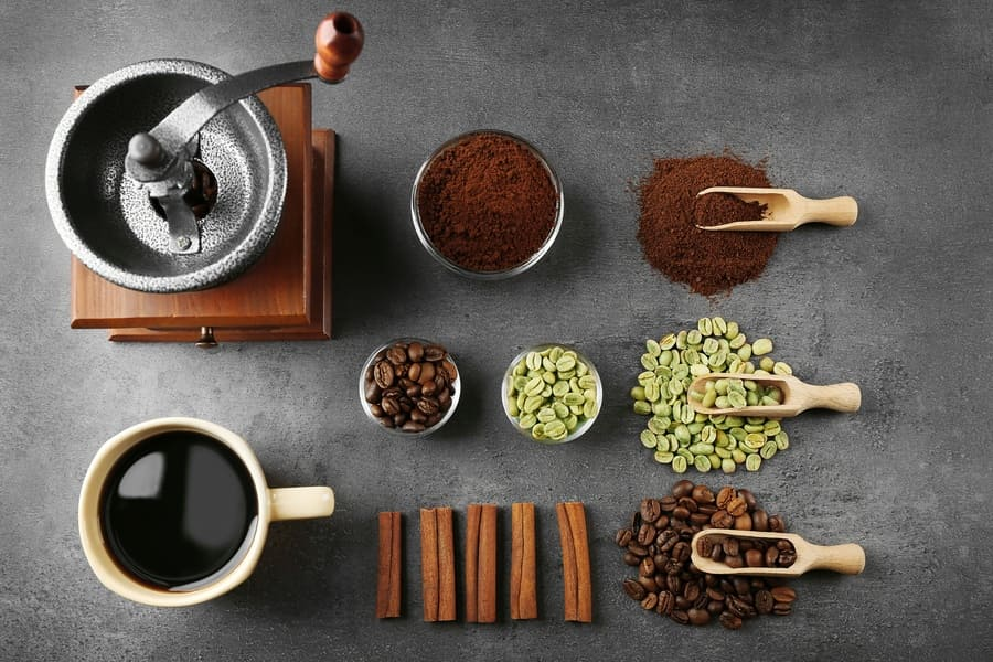 The different stages coffee can be at, including green coffee beans and some roasted and ground up