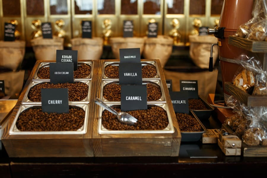 Different types of coffee beans on display for sale by weight