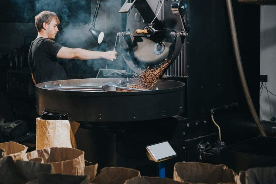 A man roasting coffee beans in a large industrial-sized machine.