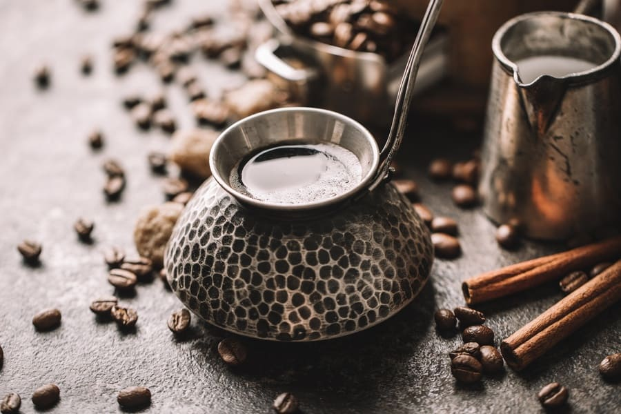 A coffee cup and coffee beans sitting on a table