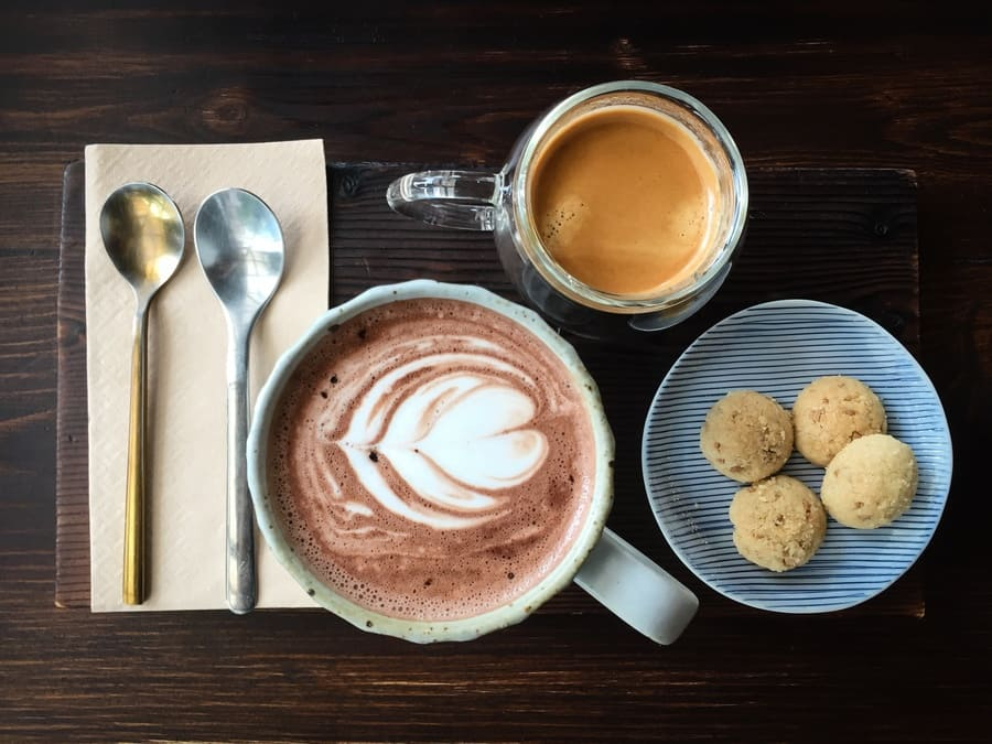 A cup of coffee next to espresso and cookies on a wooden table