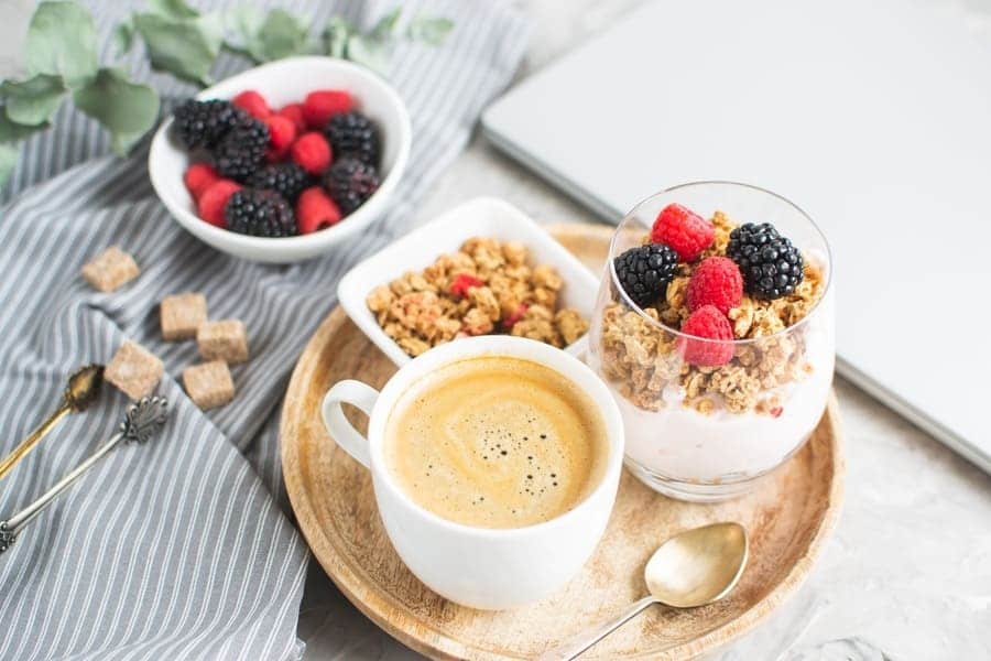 A cup of coffee next to yogurt, oats, and fresh berries
