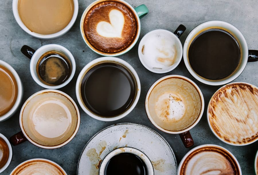 Multiple cups of coffee sitting on a grey table