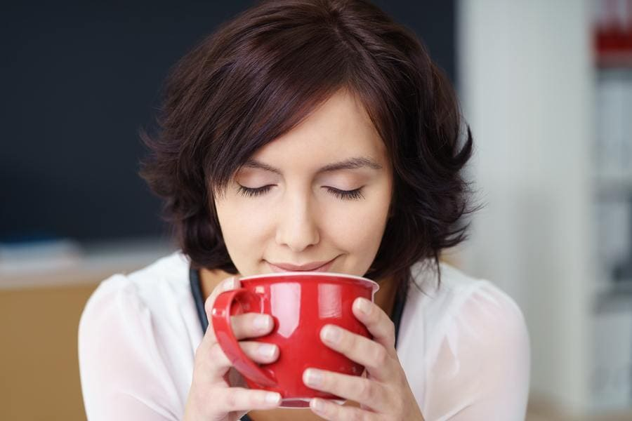 A woman having a cup of coffee and enjoying the smell with her eyes closed