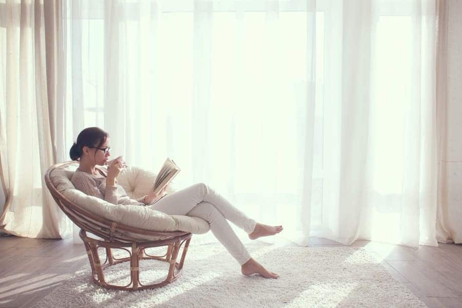 A woman sitting and reading a book in a white room with her cup of coffee