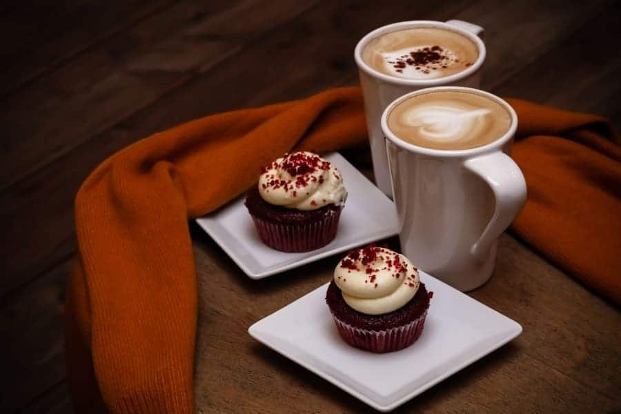 Two cups of coffee sitting next to red velvet cupcakes