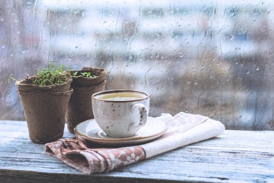 A cup of coffee sitting next to a window with rain pouring down it