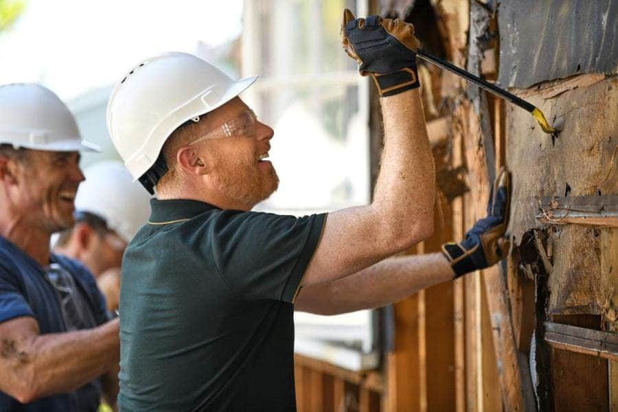 Jesse Tyler Ferguson is taking down the wall in a white hard hat using a crowbar.