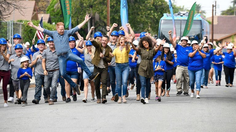 Jesse Tyler Ferguson jumping and clicking his heels together in front of the team of volunteers coming to help renovate a house on Extreme Makeover: Home Edition, 2020.