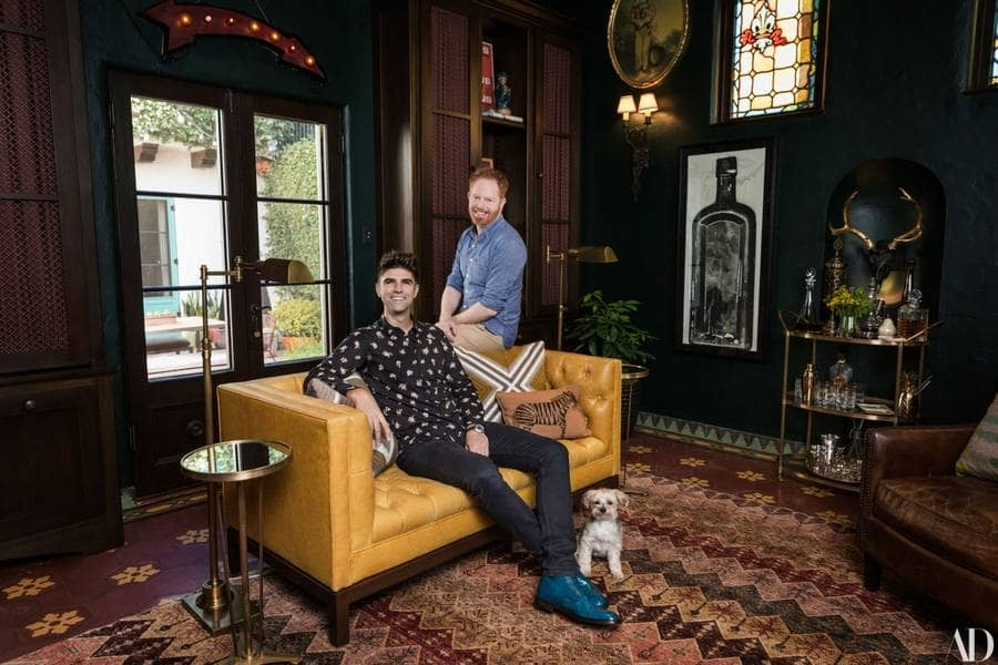Jesse Tyler Ferguson and Justin Mikita are in their living room posing for Architectural Digest.