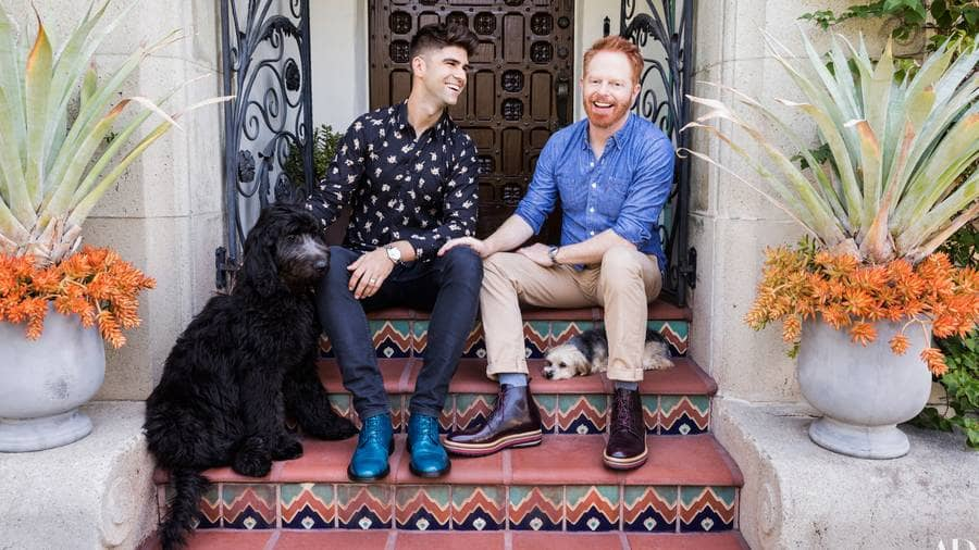 Jesse Tyler Ferguson and Justin Mikita with their dogs sitting on their front step.