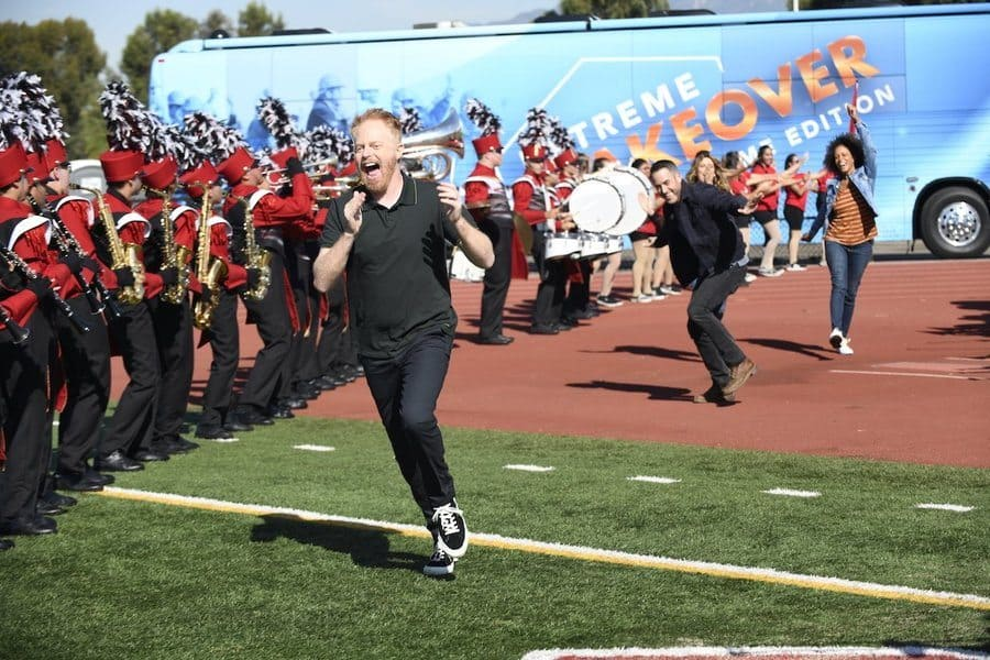 Host Jesse Tyler Ferguson on the new version of Extreme Makeover: Home Edition running through a football field with the band behind him.
