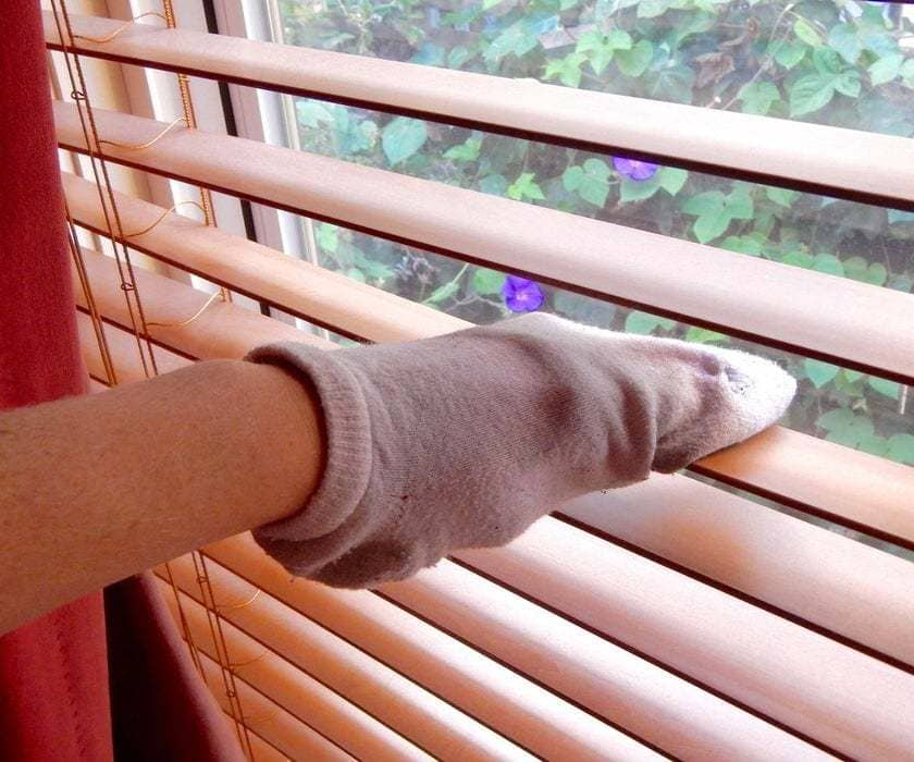 Cleaning a window by using a sock on the hand