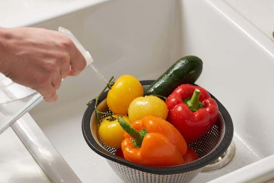 Someone is spraying peppers, tomatoes, and a zucchini in a strainer inside of the sink.