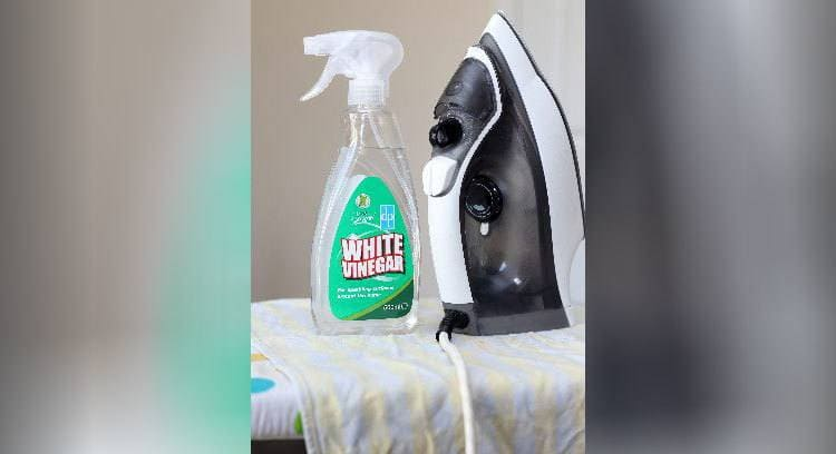 A bottle of white vinegar next to an iron, sitting on an ironing board.