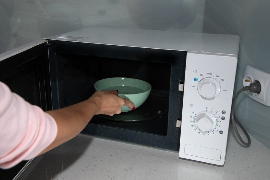 Someone is placing a bowl filled with water and vinegar into a microwave to clean it.