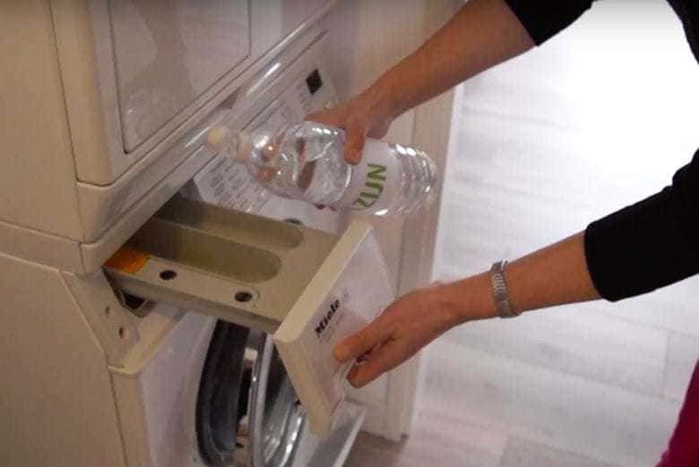 A woman is adding vinegar in the slot where the detergent goes in a washing machine.