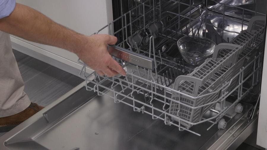 Someone is pushing the bottom shelf of the dishwasher back in with a bowl of vinegar inside.