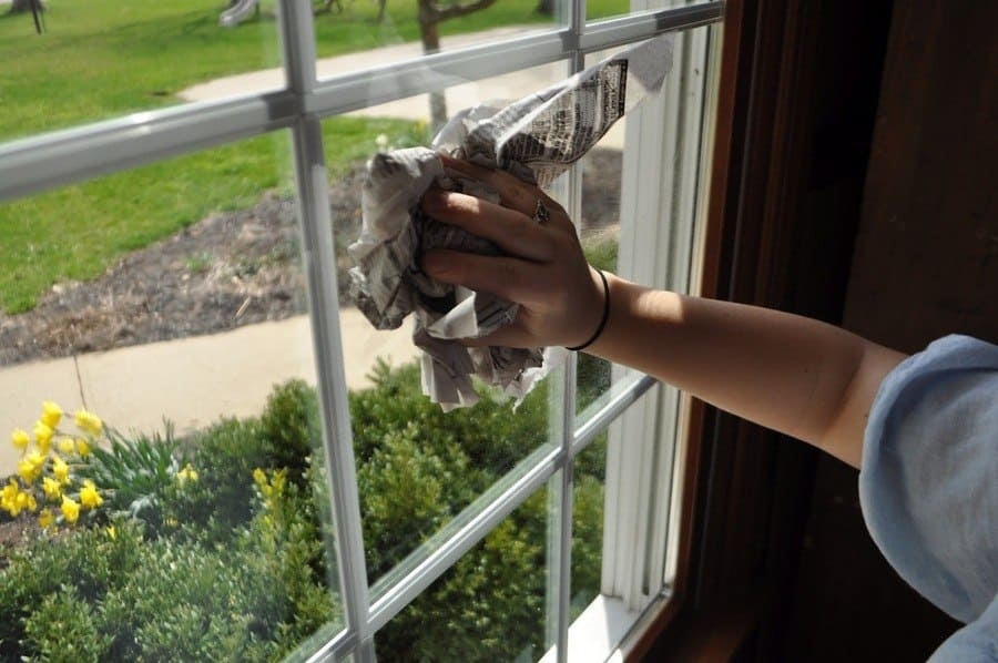 A woman using newspaper and vinegar to clean her window.
