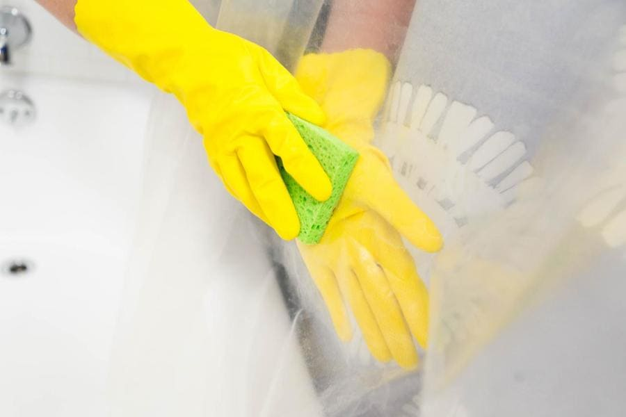 Someone wearing gloves is using a sponge to wipe vinegar on their shower liner.