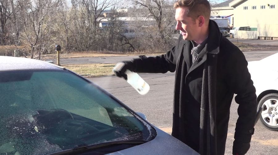 A news reporter spraying his window with vinegar to prevent frost.