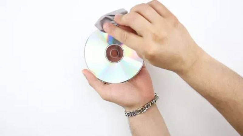 A man wiping down an old CD.