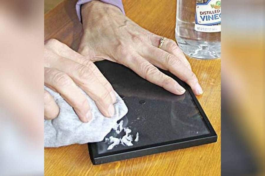 Someone is removing a sticker from a photo frame using vinegar and a cloth.